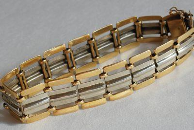 Un bracelet à maillons articulés or jaune et gris.