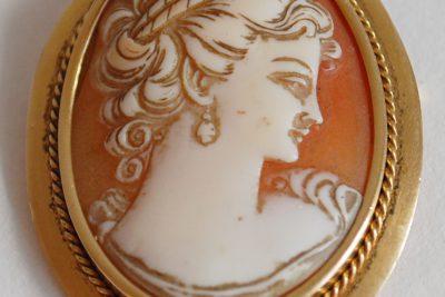 Une broche en or formant pendentif ornée d'un camée.