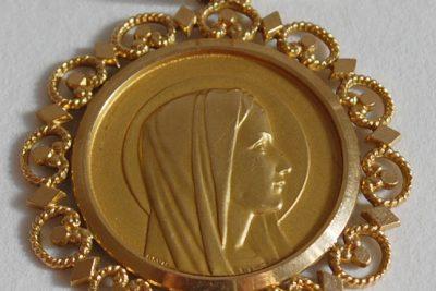 Un pendentif en or centré d'une médaille de la Vierge en or.